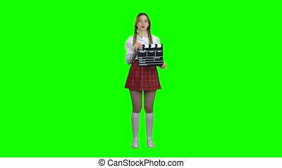 Girl is holding a clapperboard in her hands. Green screen -...