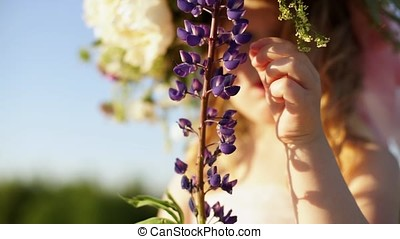 Girl is holding a lupine flower.