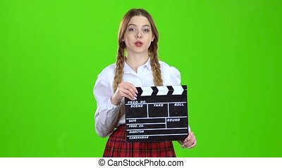 Girl is holding a movie in her hands . Green screen