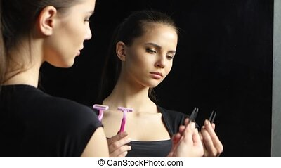 Girl is holding a shaving machine and she is upset with tweezers. Black background