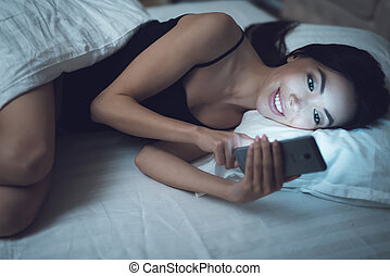 Girl is in a dark room in bed. She looks at the smartphone....