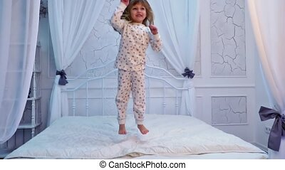 Girl is jumping on the bed