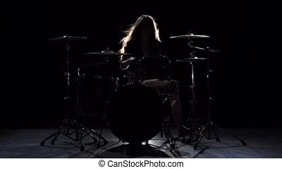 Girl is kicks from playing drums, playing energetic music. Black background. Silhouette. Slow motion