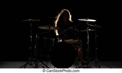 Girl is kicks from playing drums, playing energetic music. Black background. Silhouette