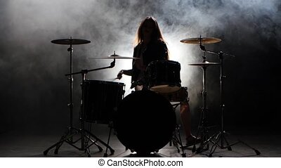 Girl is kicks from playing drums, playing energetic music. Black smoke background. Silhouette