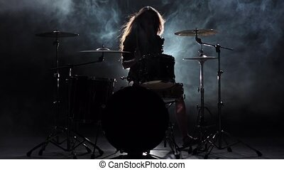 Girl is kicks from playing drums, playing energetic music. Black smoke background. Silhouette. Slow motion