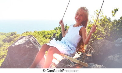 Girl is laughing on a swing. Child looking at camera.