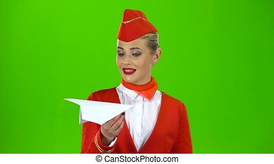 Girl launches a paper airplane, she is a flight attendant working in the airplane crew. Green screen