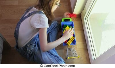 Girl is loading colorful toy bricks on the toy car
