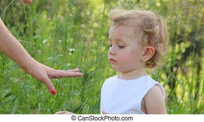 girl is looking at a ladybug, that is sitting on her mother...
