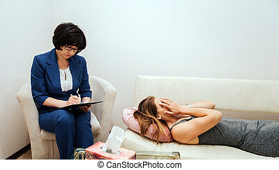 Girl is lying on sofa and covering her face with hands. She is crying. Girl is in despair. Therapist is sitting besides her and writing down information.
