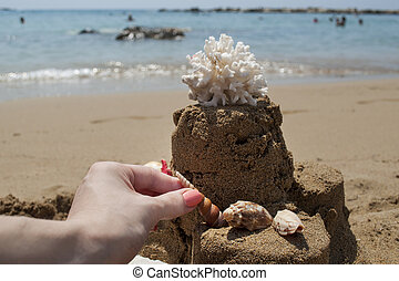 Girl is making a Sandcastle with coral on sandy beach