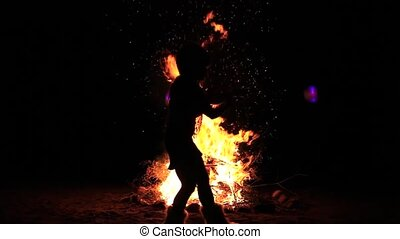Young woman performing with light pois in front of a big campfire at night. Package of 6 different scenes