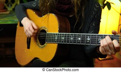 Fixed angle scene of a young girl strumming chords on an acoustic guitar in her living room. With table, plants and lights in the background