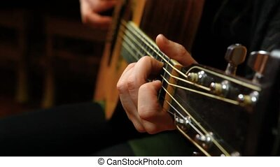 Fixed angle scene of a young girl strumming chords on an acoustic guitar in her living room.
