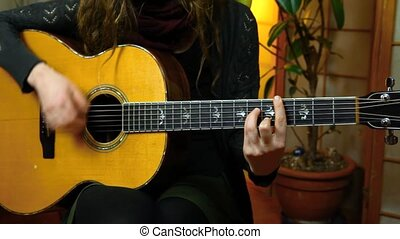 Fixed angle scene of a young girl strumming chords on an acoustic guitar in her living room. With plants in the background