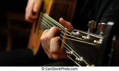 Travelling up scene of a young girl strumming chords on an acoustic guitar in her living room.