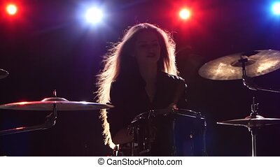 Girl is playing the drums. Black background. Red blue light from behind