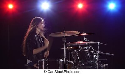 Girl is playing the drums. Black background. Red blue light from behind. Side view