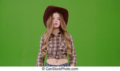 Girl is posing for cameras in the cowboy look . Green screen