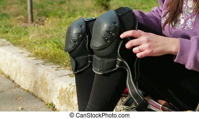 Girl Is Putting On Protective Clothing For Roller-Skating -...