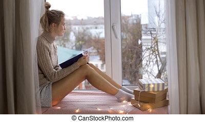 Girl is reading a book and sitting