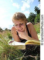 girl is reading a book on a summer meadow