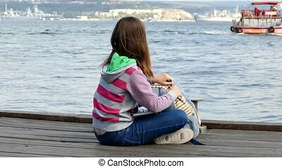 girl is reading a book on the embankment near the sea. - The...