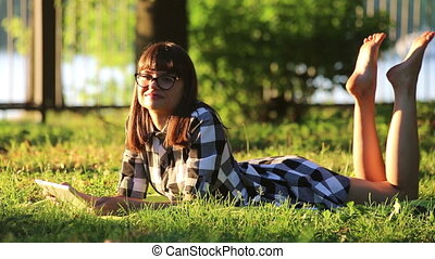 Girl is Relaxing in the Park with a Tablet PC, Lying on the Grass and Shakes her Legs