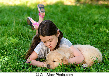 Girl is resting with her dog on the lawn
