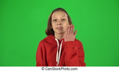 Girl is sending blow kisses and smiling on green background....