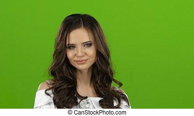 Girl is sexually flirting, biting her lip and winking. Green screen. Close up