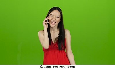 Girl is shopping with packages and talking on the phone. Green screen