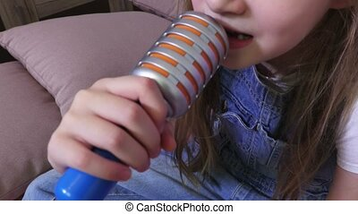 Girl is singing a song on a toy microphone