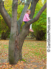 Girl is sitting on a tree