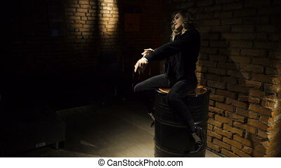 Girl is sitting on the barrel indoors