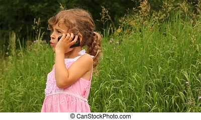 girl is speaking on her mobile phone in park - girl is...