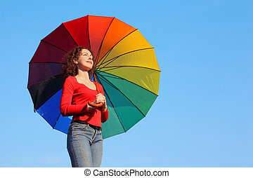 girl is standing against blue sky, holding parasol over...