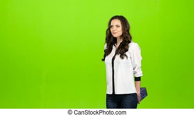 Girl is standing and waiting for her beloved guy to give him a gift. Green screen