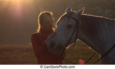 Girl is standing in the field and stroking the horse a sunset. Slow motion. Close up
