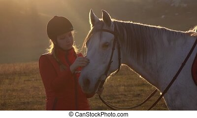 Girl is standing in the meadow and stroking the horse a beautiful sunset. Slow motion. Close up