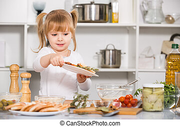 Girl is standing with salad in the kitchen