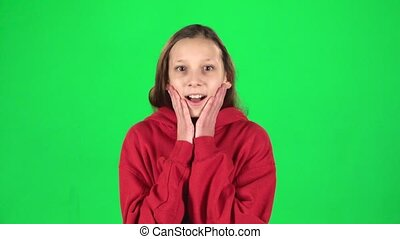 Girl is surprised and very rejoiced in studio on green background. Slow motion
