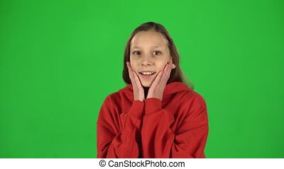 Girl is surprised and very rejoiced in studio on green background