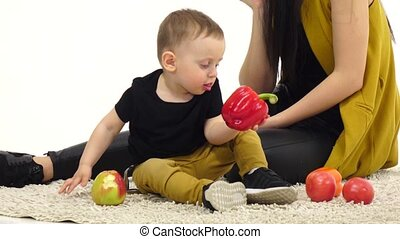 Girl is talking on the phone, her child is eating an apple. White background