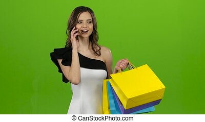 Girl is talking on the phone, she has a lot of packages in her hands. Green screen
