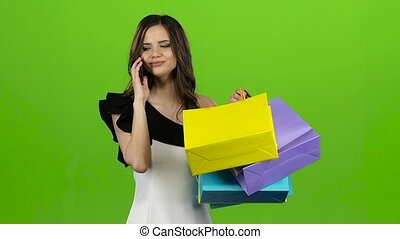 Girl is talking on the phone, she has a lot of packages in her hands. Green screen. Slow motion