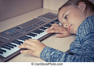 Girl is tired of learning to play the synthesizer and sad lies on the table.