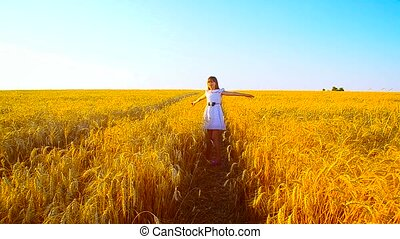 Girl is turned in the field with wheat