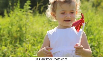 girl is turning a windmill by hand and smiling sunny and warm summer day